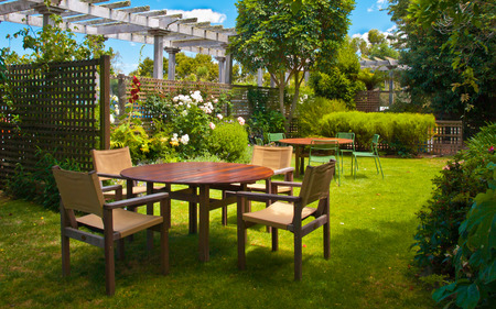 landscaped garden: Landscaped Garden with Wooden Dining Table Set in the Shade of Trees Editorial