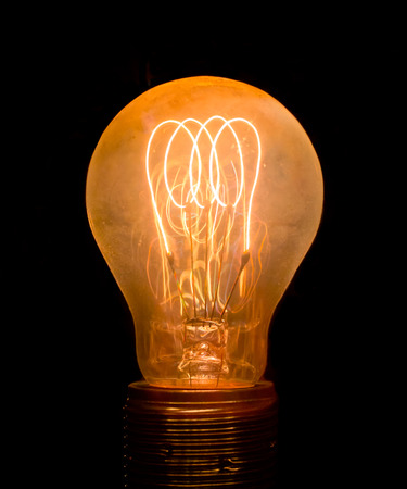 Old dusty light bulb  glowing in the dark photo
