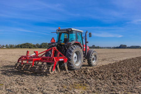 plough machine: Farming in the Netherlands, Tractor with Plough in a Field under Blue Sky