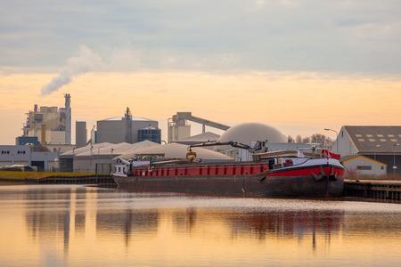 paesaggio industriale: Inland Trasporti Barge Scaricare in un impianto chimico Archivio Fotografico