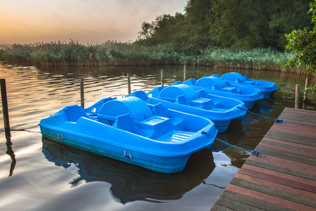 bicycle pedal: Row of Blue Pedal Rental Boats on a Foggy Morning at Zuidlaardermeer, Netherlands Stock Photo