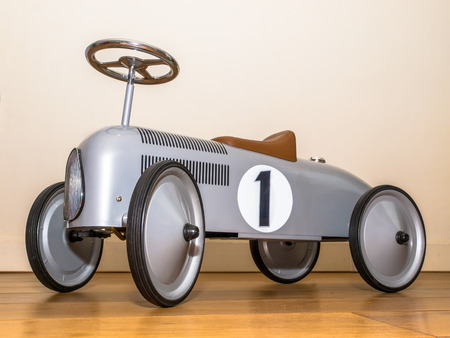 Silver Toy Push Car Against White Wall photo
