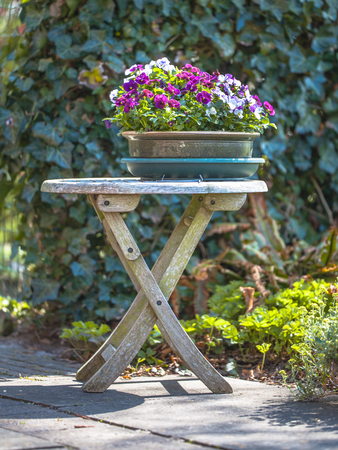 Houten tafel met bloemen in Brocante stijl in een Tuin Stockfoto - 26258990