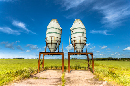 polyester: Two Fertilizer Silos in a Green Summer Field in The Netherlands Stock Photo