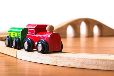 juguetes de madera: Tren de juguete de madera en el ferrocarril con puente en el telón de fondo Foto de archivo