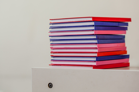 Stack of Multicolored Notebooks on a Drawer with School Furniture in Background
