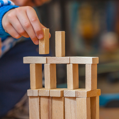 building blocks business: Boy Building a Structure from Wooden Building Blocks