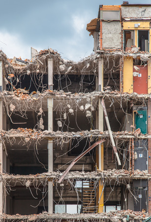 bombed city: Pieces of Metal and Stone are Crumbling from Demolished Building Floors Stock Photo