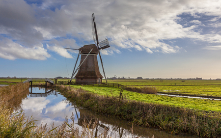 holland landscape: Traditional wooden windmill in Frisian countryside, Netherlands