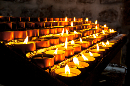 prayer candles: Votive Candles in a Group burnt to pray for Someone Else Stock Photo