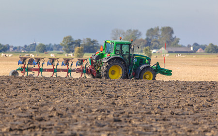 plough land: Farming in the Netherlands, Tractor with Plough in a Field with Farm and Village in Backdrop Stock Photo