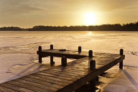 Cool Colored Sunrise above a Jetty on a Frozen Winter Lake with Ice and Snow photo