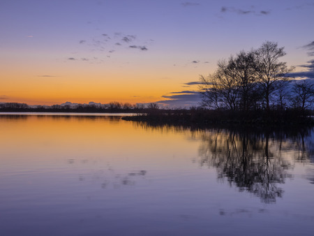 Blue and yellow Sunset over a Tranquil lake photo