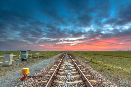 rail route: Endless railroad on the horizon under a blue and red sky as a concept for future career.