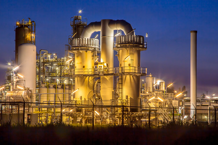 to plant: Detail of a heavy Chemical Industrial plant with mazework of pipes in twilight night scene