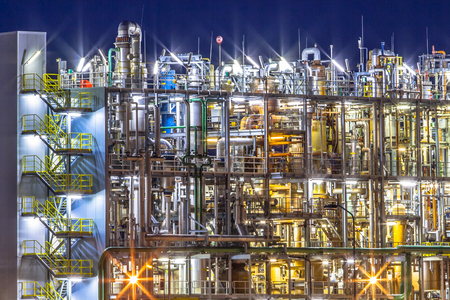 Nachtscène van detail van een zware Chemical Industrial plant met mazework van leidingen in de schemering