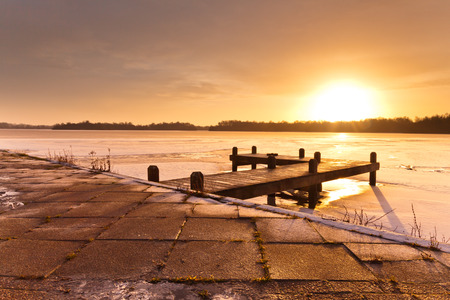 Cold Morning Sunrise above a Jetty on a Frozen Winter Lake with Ice and Snow photo