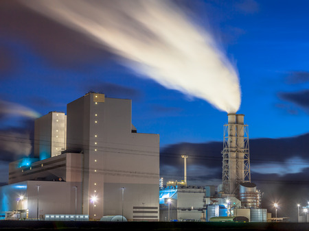 ultra modern: Ultra modern coal powered electrical power plant with smoking chimney during sunset under a blue sky