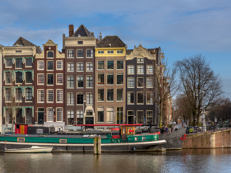 prinsengracht: Colorful traditional canal houses and boats in the UNESCO World Heritage site of Amsterdam on the corner of Amstel and Nieuwe Prinsengracht Editorial
