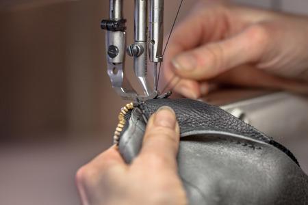 Handen die aan een lederen schoudertas op een naaimachine in een workshop Stockfoto