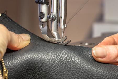 cuero vaca: Manos que trabajan en una máquina de coser de cuero en acción