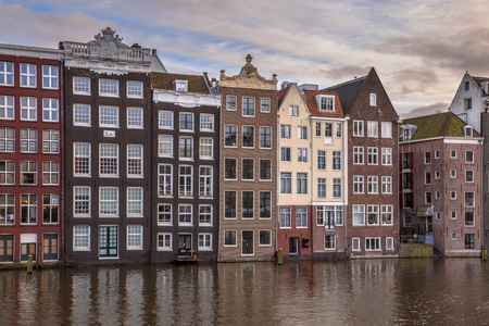north holland: Colorful traditional canal houses on the waterfront on Damrak in Amsterdam Stock Photo