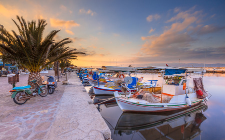 skiathos: Greek fishing harbor scene with boats, palm trees and scooters at sunrise on a beautiful tranquil summer day in july Stock Photo