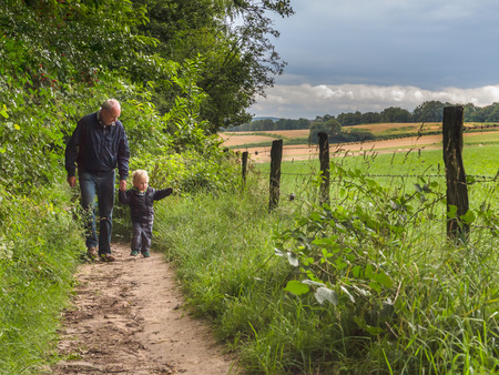 biotope: grandfather is walking with child on a walking track with family in nature Stock Photo