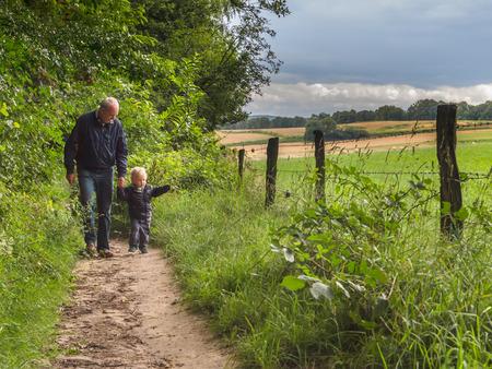 Grootvader is wandelen met kind op een wandelparcours met familie in de natuur Stockfoto - 36497314