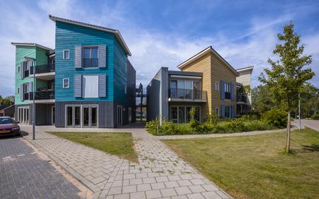 Pavement en het park met bomen in een straat met moderne houten huizen. Hedendaagse architectuur is heel gebruikelijk in Nederland Redactioneel