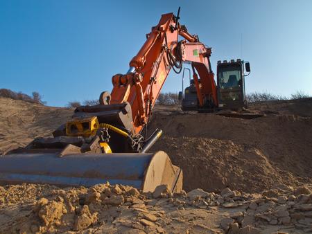 Orange colored heavy construction digger Stock fotó