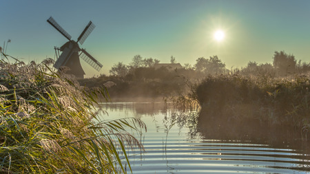marken: Characteristic historic windmill in hazy wetland on a foggy september morning in the Netherlands Stock Photo