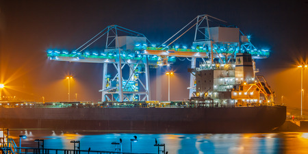Nautical ship on a wharf during twilight is unloaded with huge modern cranes under colorful lighting photo