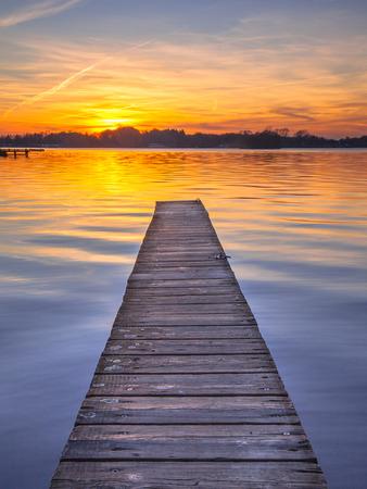 湖 Paterwoldsemeer の穏やかな水に沈む夕日