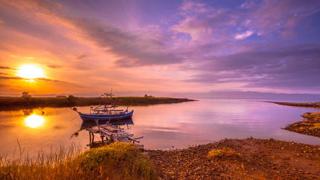 horizon over water: Fishing boat in a river inlet bay during orange sunrise on Lesbos island, Greece