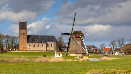 leeuwarden: Village of Wanswert with church an historic windmill on Frisian countryside. Just North of Leeuwarden, Friesland Stock Photo
