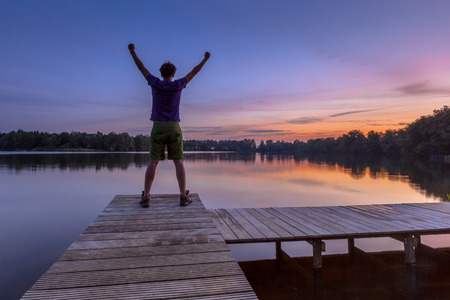 grateful: Man raising his arms while enjoying the sunset as a concept for a happy achievement Stock Photo