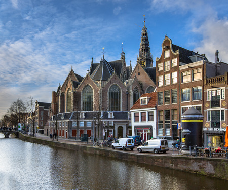 canal houses: colorful historic canal houses and the old church or oude kerk on the oudezijds voorburgwal in Amsterdam
