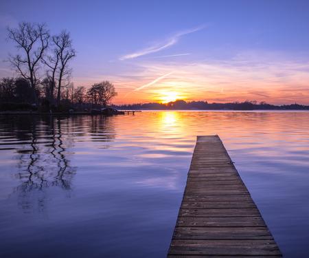 wooden dock: Sunset over Serene Water of Lake Paterwoldsemeer