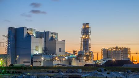 Ultra moderne kolen aangedreven elektriciteitscentrale tijdens zonsondergang onder een blauwe en oranje hemel Stockfoto