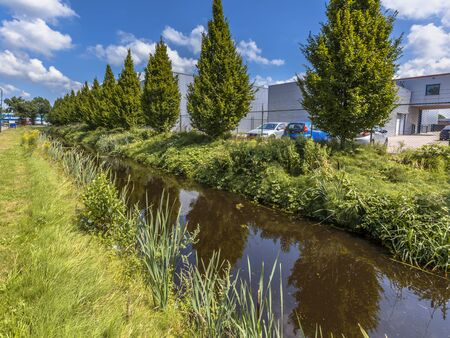 scenic  landscape: Excessive rainwater discharge draining canal in a dutch industrial area in Soest, Netherlands