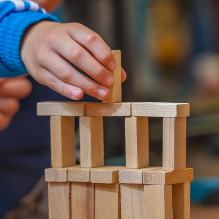 establishes: Boy Building a Structure from Wooden Building Blocks