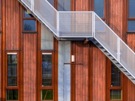 Escape stairs on a sustainable wooden office building background Stockfoto