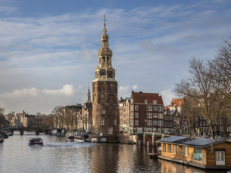 canal houses: The tower Montelbaanstoren with houseboats and historic canal houses in Amsterdam