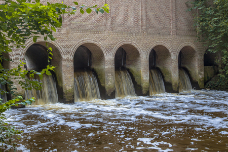 canal house: Water streaming through the Famous Sluice house or schuivenhuisje at Almelo Nordhorn Canal in Twente