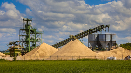 aggregates: Construction sand mining terminal with conveyer belts and silos on a clouded summer day