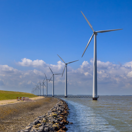 flevoland: Long row of wind turbines positioned in water offshore along the coast