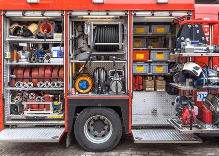 Slangen, kleppen en andere inventaris van een brandweerwagen Stockfoto