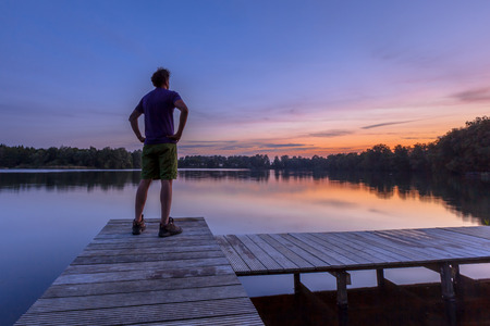 hopefulness: Man overlooking lake with arms on hips as a concept for concern and hopefulness