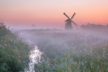 traditional windmill: Polder landscape with Characteristic traditional windmill on a foggy september morning in the Netherlands Stock Photo